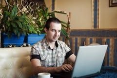 Equipaggi il lavoro in un caffè su un computer portatile Immagini Stock Libere da Diritti