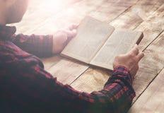 Equipaggi il libro di lettura che si siede ad una tavola di legno Fotografia Stock Libera da Diritti