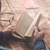 Equipaggi il libro di lettura che si siede ad una tavola di legno Fotografia Stock