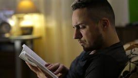 Equipaggi il libro di lettura che si siede sul sofà alla notte a casa stock footage