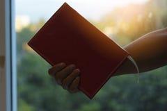 Equipaggi il libro e lo smartphone della tenuta nella stanza di vetro con il fondo del tramonto Immagini Stock