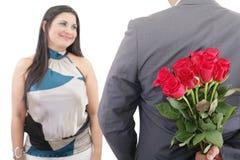 Equipaggi il mazzo nascondentesi di rose rosse dietro il suo di nuovo alla sorpresa Immagini Stock Libere da Diritti