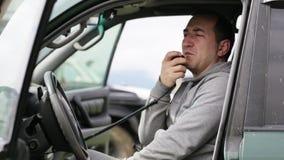 Equipaggi il microphon della mano della tenuta e la conversazione sulla radio in sua automobile stock footage