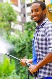 Equipaggi il modello quadrato d'uso blu e la camicia bianca che tiene la pistola a acqua ad alta pressione, indicante il liquido  Fotografia Stock