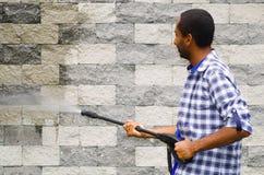 Equipaggi il modello quadrato d'uso blu e la camicia bianca che tiene la pistola a acqua ad alta pressione, indicante verso il mu Immagini Stock