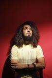 Equipaggi il modo ed i bei capelli ricci lunghi contro fondo rosso Fotografie Stock Libere da Diritti