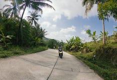 Equipaggi il motorino della bici dell'azionamento sulla strada con le palme in Tailandia fotografie stock