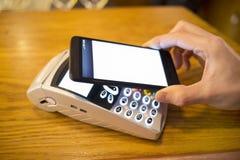 Equipaggi il pagamento con la tecnologia di NFC sul telefono cellulare, il ristorante, negozio Immagine Stock