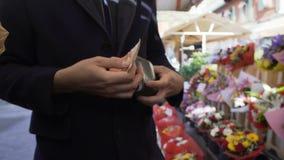 Equipaggi il pagamento dei soldi per fiorire il venditore del mercato per il mazzo elegante per il suo caro stock footage