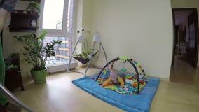 Equipaggi il pavimento pulito con l'aspirapolvere ed il bambino curioso sulla stuoia del gioco 4K video d archivio