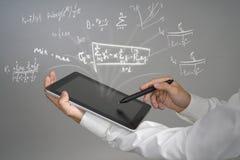 Equipaggi il PC ed il funzionamento della compressa della tenuta dello studente o dello scienziato con i vari per la matematica d Fotografia Stock