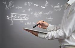 Equipaggi il PC ed il funzionamento della compressa della tenuta dello studente o dello scienziato con i vari per la matematica d Fotografia Stock Libera da Diritti