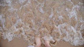Equipaggi il piede nudo di camminata sulla spiaggia sabbiosa nell'onda di oceano, punto di vista video d archivio