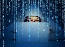 Equipaggi il pirata informatico che lavora ad un computer portatile sul fondo di codice binario Immagine Stock Libera da Diritti
