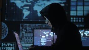 Equipaggi il pirata informatico del geek in cappuccio che funziona al computer nel centro cyber di sicurezza riempito di schermi  video d archivio