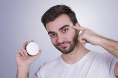Equipaggi il prodotto di bellezza, uomo che applica la crema di fronte Immagine Stock