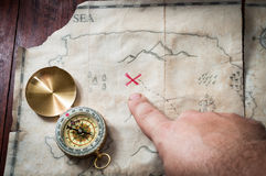 Equipaggi il punto con il dito nella croce rossa sulla mappa antica del tesoro con la bussola sullo scrittorio di legno Immagine Stock