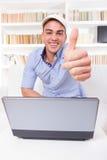 Equipaggi il rilassamento a casa con il computer portatile che mostra i pollici su Fotografie Stock