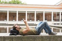 Equipaggi il rilassamento e lo sguardo del computer della compressa nella via fotografia stock libera da diritti