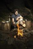 Equipaggi il rilassamento nella regione selvaggia con la chitarra e la preparazione del pesce cercato fotografie stock