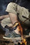 Equipaggi il rilassamento nella regione selvaggia e la preparazione del pesce cercato su fuoco immagine stock libera da diritti