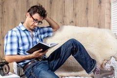 Equipaggi il rilassamento sul libro novello di storia della lettura dello strato del sofà Immagini Stock