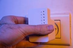 Equipaggi il ripetitore di WiFi dell'inserzione nell'incavo elettrico sulla parete immagine stock