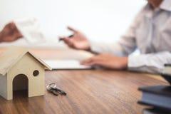 Equipaggi il segno una polizza d'assicurazione domestica sui prestiti immobiliari, tenuta dell'agente dell'agente Fotografia Stock