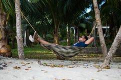 Equipaggi il sonno su un'amaca o una rete vicino su una spiaggia Immagine Stock