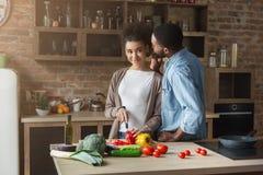 Equipaggi il sussurro in orecchio del ` s della moglie mentre cucinano fotografia stock libera da diritti