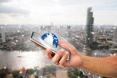 Equipaggi il telefono cellulare della tenuta della mano del ` s con il globo sul fondo vago della città Fotografie Stock Libere da Diritti