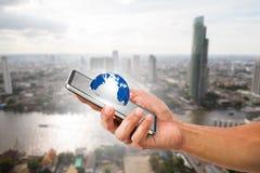 Equipaggi il telefono cellulare della tenuta della mano del ` s con il globo sul fondo vago della città Fotografia Stock Libera da Diritti