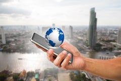 Equipaggi il telefono cellulare della tenuta della mano del ` s con il globo sul fondo vago della città Immagini Stock Libere da Diritti