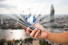 Equipaggi il telefono cellulare della tenuta della mano del ` s con il globo sul fondo vago della città Immagine Stock Libera da Diritti