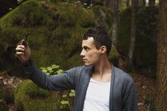 Equipaggi il telefono cellulare di uso, immagine di sfuocatura dei turisti camminano nella foresta come fondo Immagini Stock