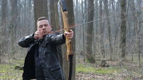 Equipaggi il tiro con un arco nella foresta stock footage
