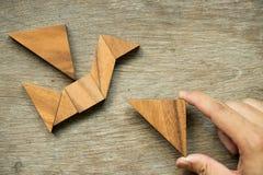 Equipaggi il triangolo della tenuta per compiere il puzzle del tangram nella forma dell'uccello Immagini Stock
