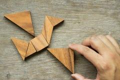 Equipaggi il triangolo della tenuta per compiere il puzzle del tangram nella forma dell'uccello Fotografia Stock