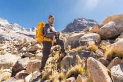 Equipaggi il turista di viaggiatore con zaino e sacco a pelo che sta posante la sommità della neve delle rocce della montagna, Bo Fotografia Stock Libera da Diritti