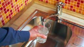Equipaggi il versamento del vetro di acqua dolce da un rubinetto della cucina stock footage