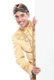 Equipaggi il vestito tradizionale d'uso di Java che si nasconde dietro il bianco in bianco Immagini Stock