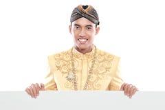 Equipaggi il vestito tradizionale d'uso di Java che tiene il bordo in bianco immagine stock libera da diritti