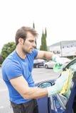 Equipaggi il vetro dell'automobile di pulizia con la spugna ed acqua fotografia stock