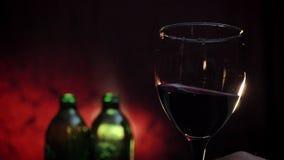Equipaggi il vetro di tenuta e d'ondeggiamento della mano del ` s di vino rosso al rallentatore, di due bottiglie e di fondo ross stock footage