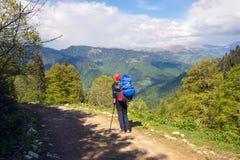 Equipaggi il viaggiatore con il grande zaino sulla strada della montagna Immagini Stock Libere da Diritti