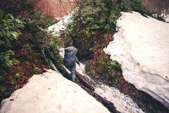 Equipaggi il viaggiatore con la cascata dell'incrocio dello zaino ed il ghiacciaio della neve Fotografie Stock