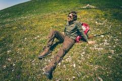 Equipaggi il viaggiatore con lo zaino che si rilassa sull'erba della valle Fotografia Stock Libera da Diritti