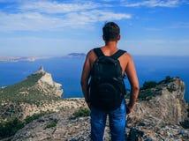 Equipaggi il viaggiatore con lo zaino che sta sopra una montagna e che guarda fuori al mare Fotografia Stock