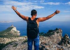 Equipaggi il viaggiatore con lo zaino che sta sopra una montagna con le mani sollevate su Fotografia Stock