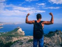 Equipaggi il viaggiatore con lo zaino che sta con il suo di nuovo al precipizio della montagna Immagine Stock Libera da Diritti